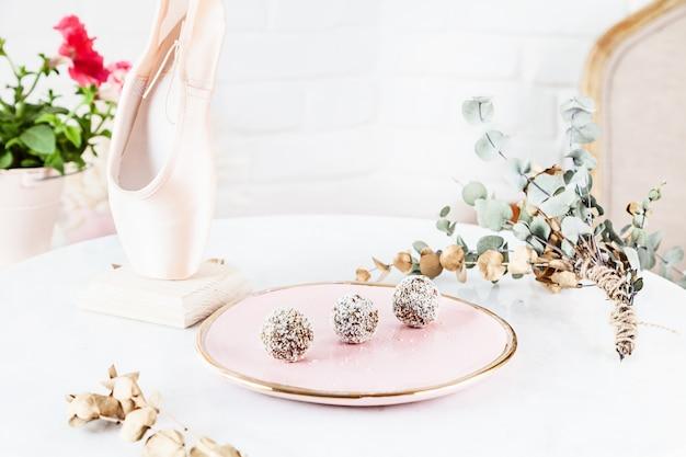Het vegetarische gezonde suikergoed met wortel diende op roze plaat boven witte achtergrond. sluit omhoog horizontale voedselfoto. glutenvrij, gezond dessert. veganistisch eten en snoep. snack. kopieer ruimte