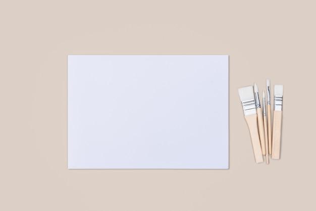 Het vel is puur wit en de verfkwasten staan op een beige achtergrond met een plek om te kopiëren. mock-up, mockup, lay-out.