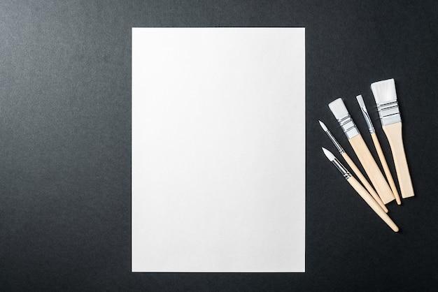 Het vel is puur wit en de verfkwasten staan op een zwarte achtergrond met een plek om te kopiëren. mock-up, mockup, lay-out.
