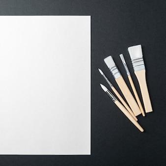 Het vel is puur wit en de verfkwasten staan op een zwarte achtergrond met een plek om te kopiëren