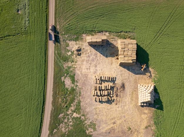 Het veld met balen stro in de stapel na het oogsten van het graan. bovenaanzicht. natuurlijke ecologische brandstof en meststoffen voor landbouwwerkzaamheden.