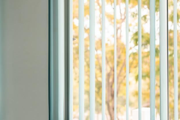 Het venster van het venster verblindt gordijn met de kleurenmening en zonlicht van de aardherfst