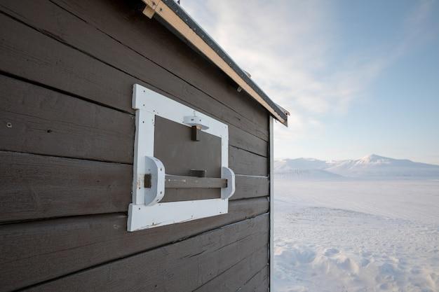 Het vensterblind van de ijsbeer op een kleine cabine in svalbard, noorwegen
