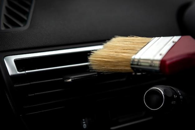 Het ventilatierooster van de auto-airconditioner met borstel schoonmaken.