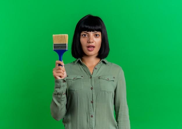 Het verbaasde jonge donkerbruine kaukasische meisje houdt verfborstel die op groene achtergrond met exemplaarruimte wordt geïsoleerd