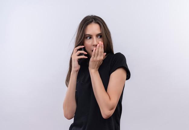 Het verbaasde jonge kaukasische meisje dat zwarte t-shirt draagt, spreekt over telefoon behandelde mond op geïsoleerde witte achtergrond