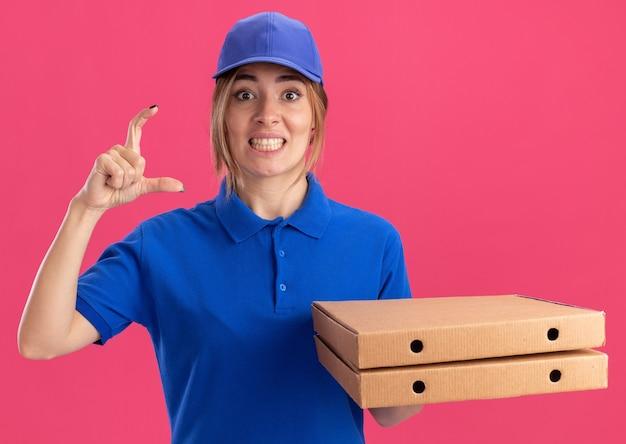 Het verbaasde jonge mooie bezorgmeisje in uniform met pizzadozen doet alsof ze iets op roze vasthoudt