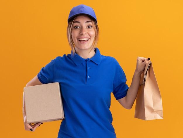 Het verbaasde jonge mooie leveringsmeisje in uniform houdt document pakket en kartondoos op oranje