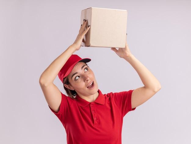 Het verbaasde jonge mooie leveringsmeisje in uniform houdt kartonnen doos boven het hoofd op wit
