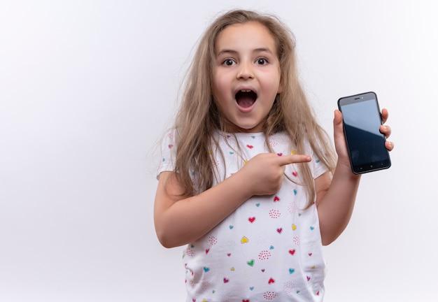 Het verbaasde kleine schoolmeisje dat witte t-shirt draagt wijst naar telefoon op geïsoleerde witte achtergrond