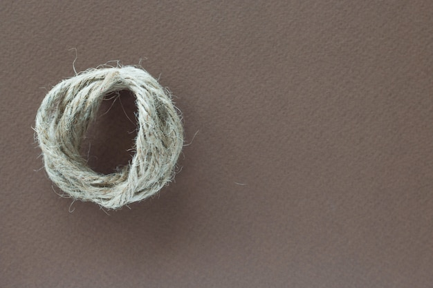 Het verdraaide witte touw op bruine achtergrond