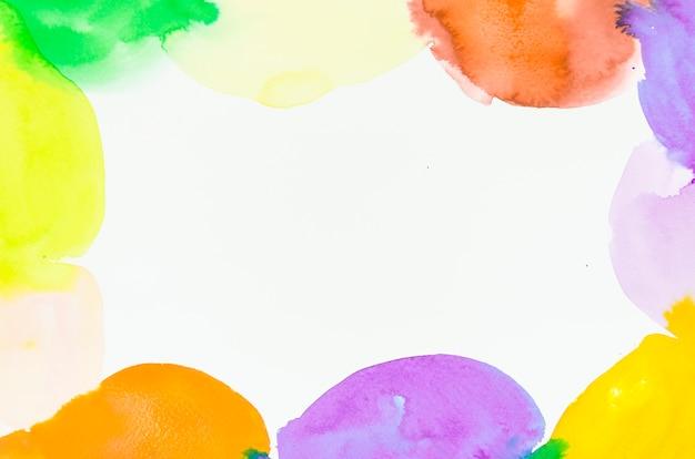 Het verfraaide kleurrijke kader van waterverfvlekken op witte achtergrond