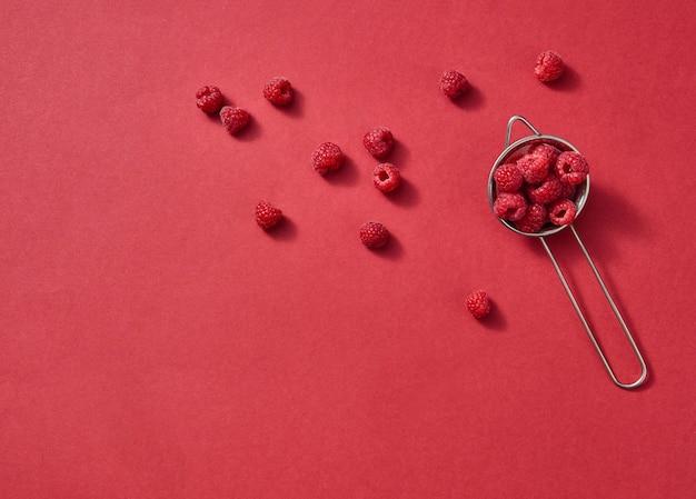 Het vergiet met sappige rijpe bessen voor het koken van heerlijke zelfgemaakte taart op een rode papieren achtergrond met kopieerruimte.