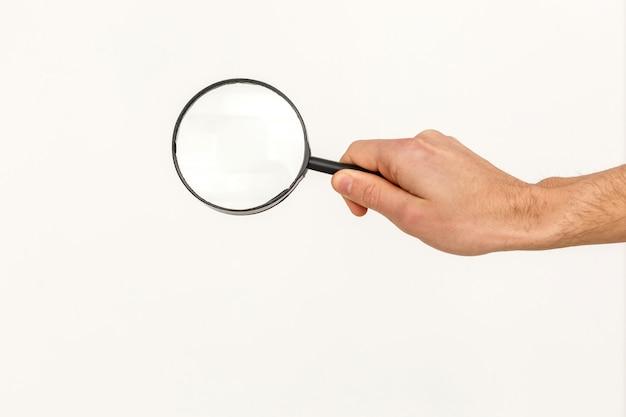 Het vergrootglas van de handholding op witte achtergrond wordt geïsoleerd die