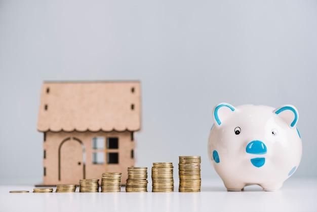 Het vergroten van gestapelde munten; spaarpot en huis model op wit reflecterend bureau