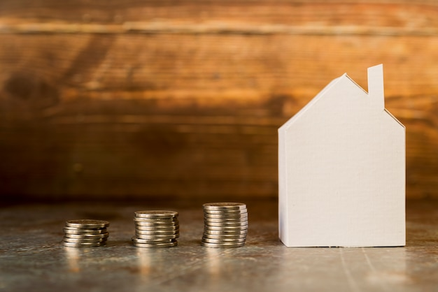 Het verhogen van stapel munten in de buurt van het papier huis op het oppervlak