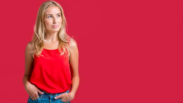 Het verleidelijke vrouw stellen in rood mouwloos onderhemd met exemplaarruimte