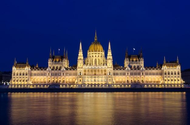 Het verlichte hongaarse parlement van boedapest bij nacht dacht in de rivier van donau na.