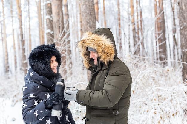 Het verliefde paar drinkt een warme drank uit een thermoskan en geniet van de winterse natuur.