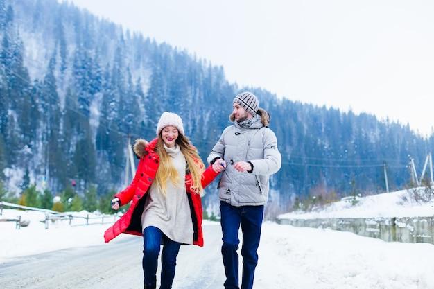 Het verliefde paar houdt elkaars hand vast en heeft plezier terwijl ze over de winter bergweg rennen