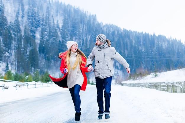 Het verliefde paar houdt elkaars hand vast en kijkt elkaar aan terwijl ze over een winterse bergweg rennen