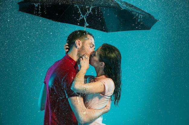 Het verliefde paar in de regen met paraplu op een turkooizen achtergrond