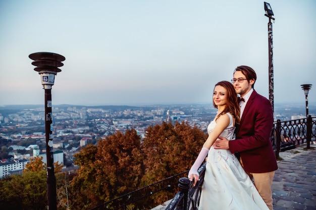 Het verliefde paar kijkt vanaf het observatieterras uit op de avondstad