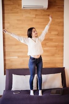 Het vermoeide aantrekkelijke vrouwenwerk die thuis wapens uitrekken om na zware dag te ontspannen