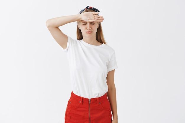 Het vermoeide jonge blonde meisje stellen tegen de witte muur