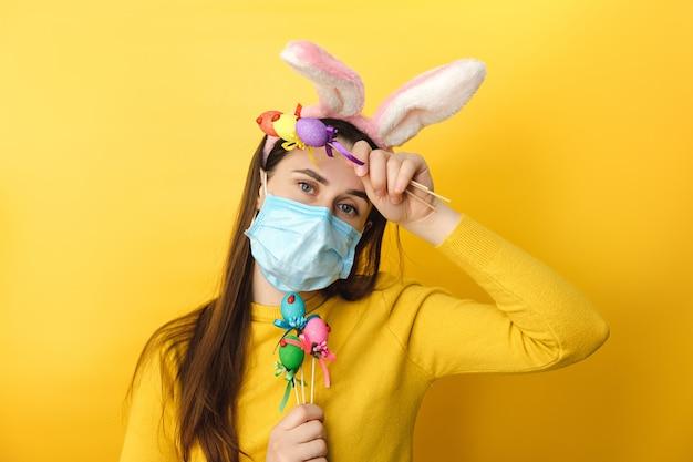 Het vermoeide jonge wijfje die konijntjesoren met virusmasker dragen, houdt gekleurde eggpt.