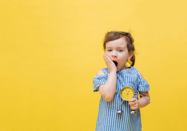 Het vermoeide meisje op een gele ruimte houdt een wekker. een klein meisje geeuwt op een gele ruimte. leuk meisje met pigtails in een gestreepte blouse.