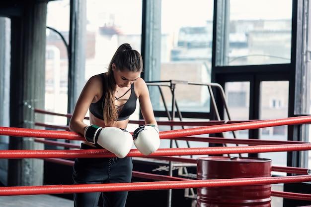 Het vermoeide sportmeisje leunde op rode touwen op de boksring en rust uit na een zware training in een zwarte gymzaal. gezond en sportief levensstijlconcept.