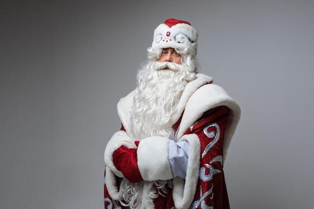 Het vermoeide stellen van de kerstman op grijze studio