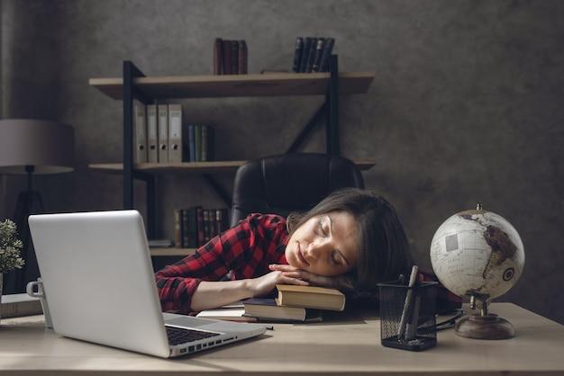 Het vermoeide studentenmeisje slaapt thuis over haar boeken