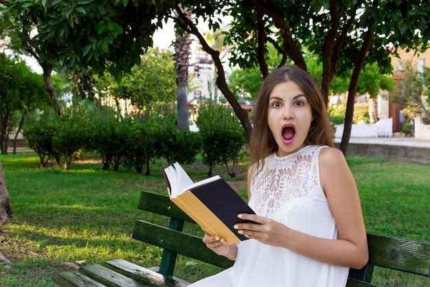 Het verraste jonge meisje met een brede geopende mond leest een boek in het park