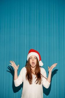 Het verraste kerstmismeisje dat een santahoed op de blauwe achtergrond draagt