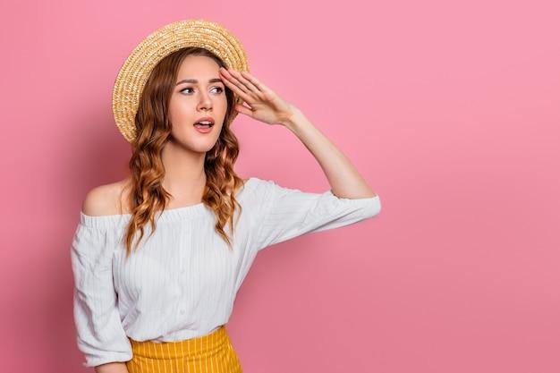 Het verraste meisje in een strohoed kijkt weg geïsoleerd op een roze muur. een jonge vrouw in zomerkleding zoekt kortingen. het meisje is geschokt door de zomerverkoop