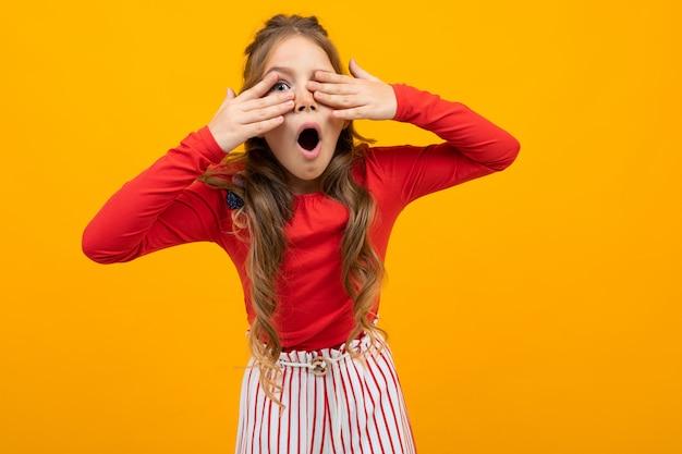 Het verraste tienermeisje met krullend haar in een rode blouse en gestreepte broek behandelt haar handen met ogen onn oranje met exemplaarruimte
