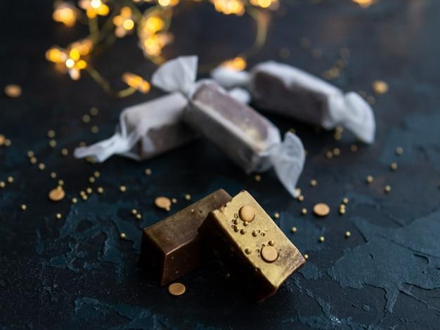 Het verse gouden suikergoed van de karameltoffee in witboek op blauwe donkere achtergrond met slinger in de vorm van lichtgevende sterren.