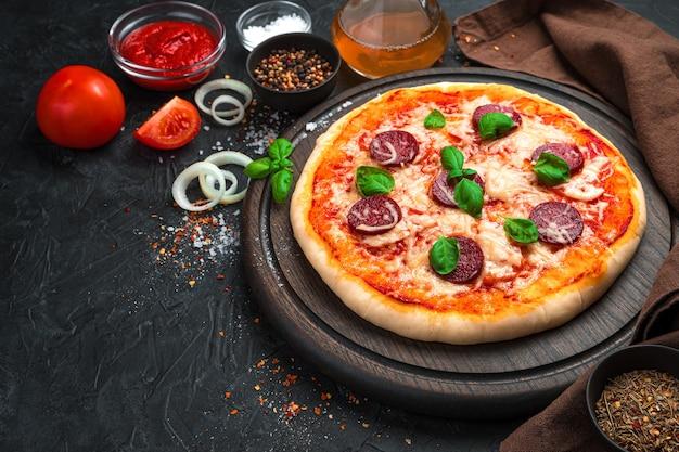 Het verse, heerlijke close-up van de pepperonispizza op een zwarte achtergrond. zijaanzicht. het concept van deeggerechten.
