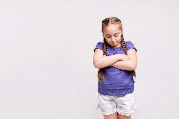 Het verstoorde meisje stellen op witte muur