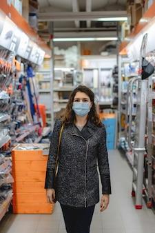 Het verticale portret die van de close-up kaukasisch vrouwen beschermend gezichtsmasker dragen die tussen de planken lopen slaan op die het winkelen doen.