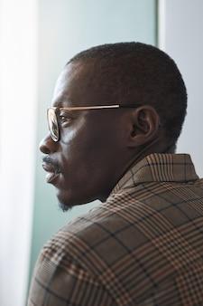 Het verticale portret van de profielmening van slimme afrikaans-amerikaanse heer die een bril draagt terwijl hij naar venster kijkt, uniek schoonheidsconcept