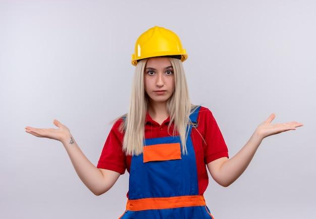 Het verwarde jonge blonde meisje van de ingenieursbouwer in uniform die lege handen op geïsoleerde witte ruimte tonen