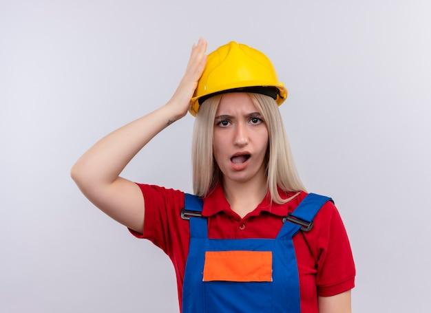 Het verwarde jonge blonde meisje van de ingenieursbouwer in uniform hand op het hoofd zetten op geïsoleerde witte ruimte
