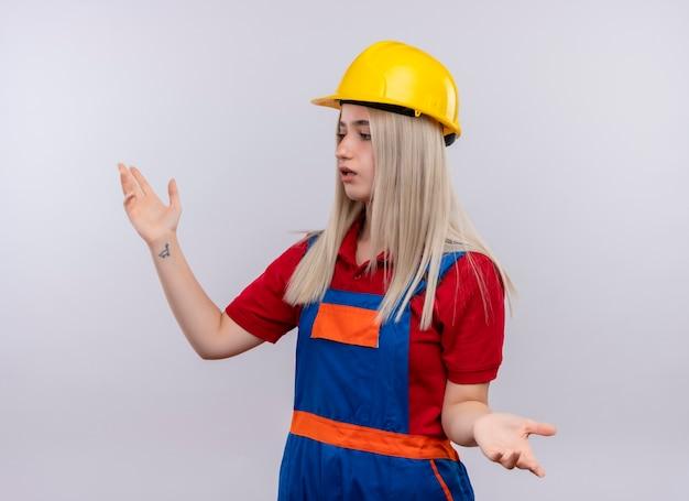 Het verwarde jonge blonde meisje van de ingenieursbouwer in uniform met open armen kijkend naar linkerkant op geïsoleerde witte ruimte