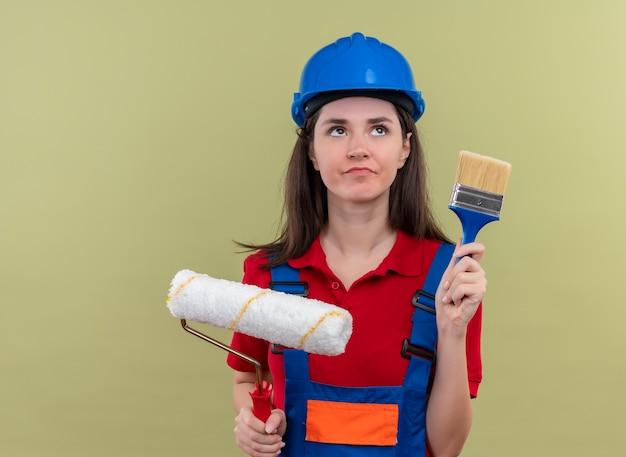 Het verwarde jonge bouwersmeisje met blauwe veiligheidshelm houdt verfroller en kwast op geïsoleerde groene achtergrond met exemplaarruimte