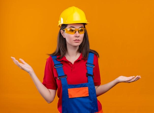 Het verwarde jonge bouwersmeisje met veiligheidsbril heft handen op geïsoleerde oranje achtergrond op