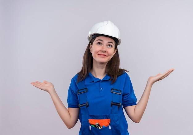 Het verwarde jonge bouwersmeisje met witte veiligheidshelm en blauw uniform houdt handen omhoog en kijkt omhoog op geïsoleerde witte achtergrond met exemplaarruimte
