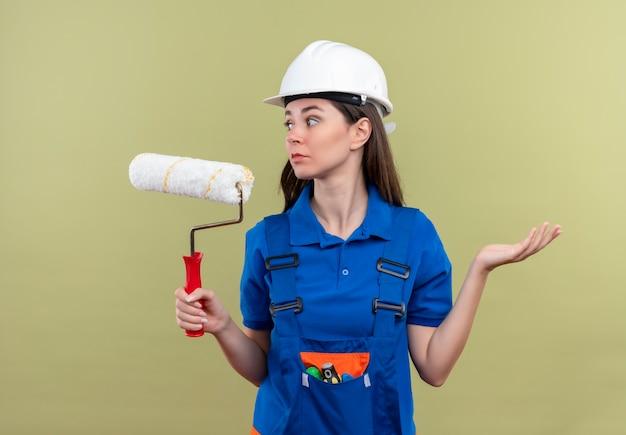 Het verwarde jonge bouwersmeisje met witte veiligheidshelm en blauw uniform houdt verfroller en kijkt naar de zijkant op geïsoleerde groene achtergrond